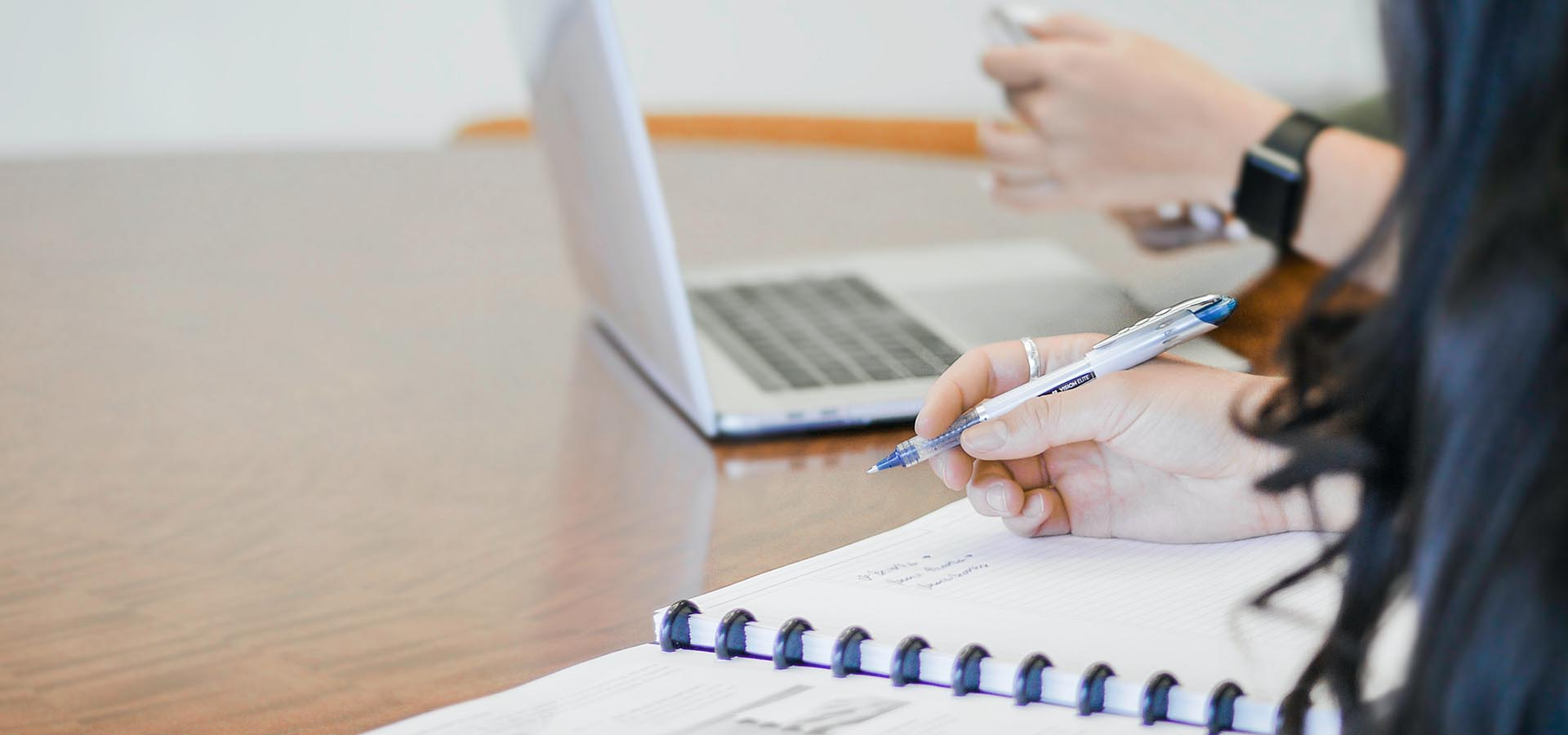 person taking notes in paper notebook with pen next to person on laptop