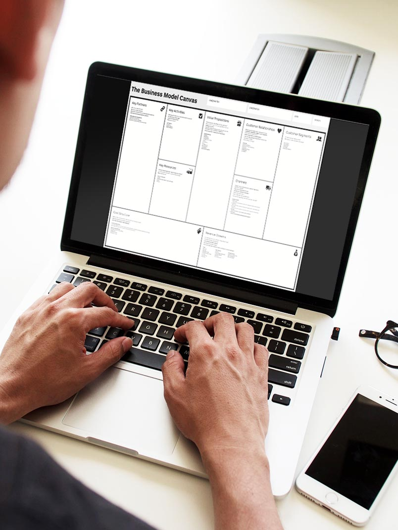 man on laptop viewing business model canvas