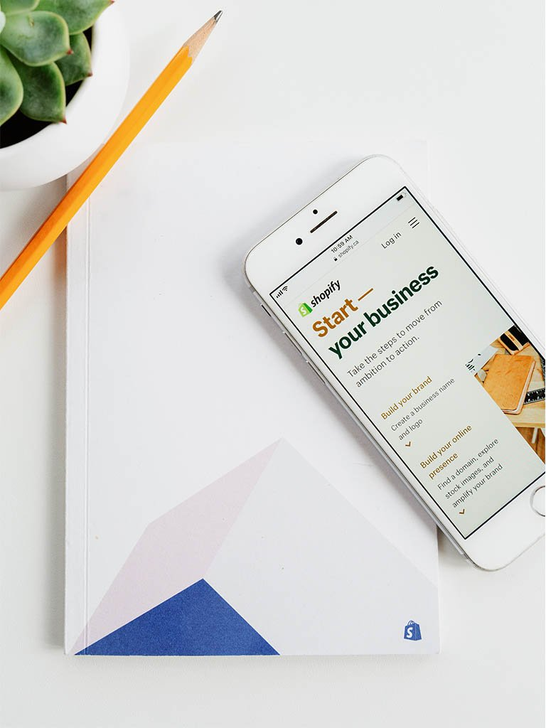 iphone on a shopify branded booklet showing shopify sample