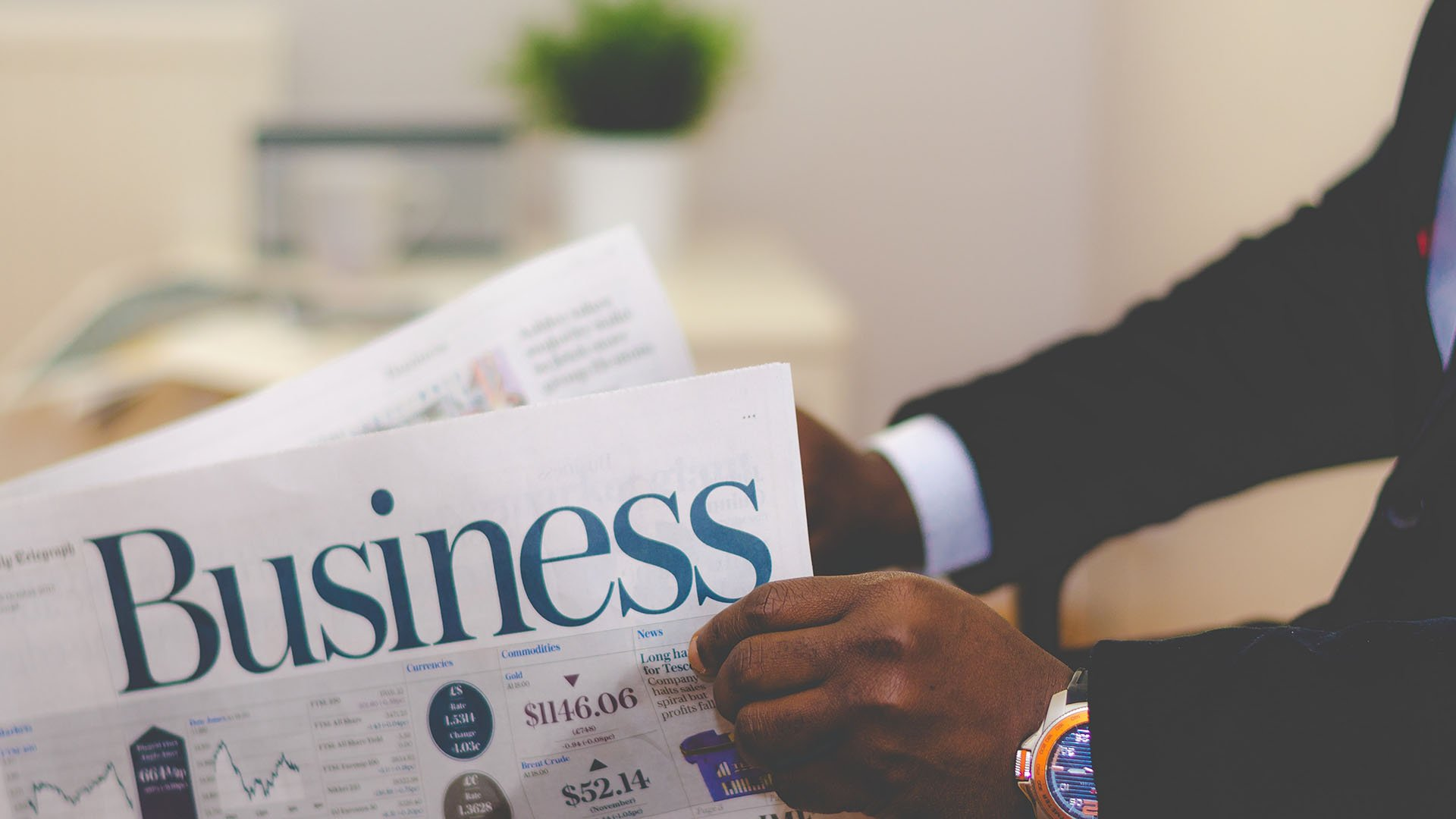 man holding news paper with business written in large letters
