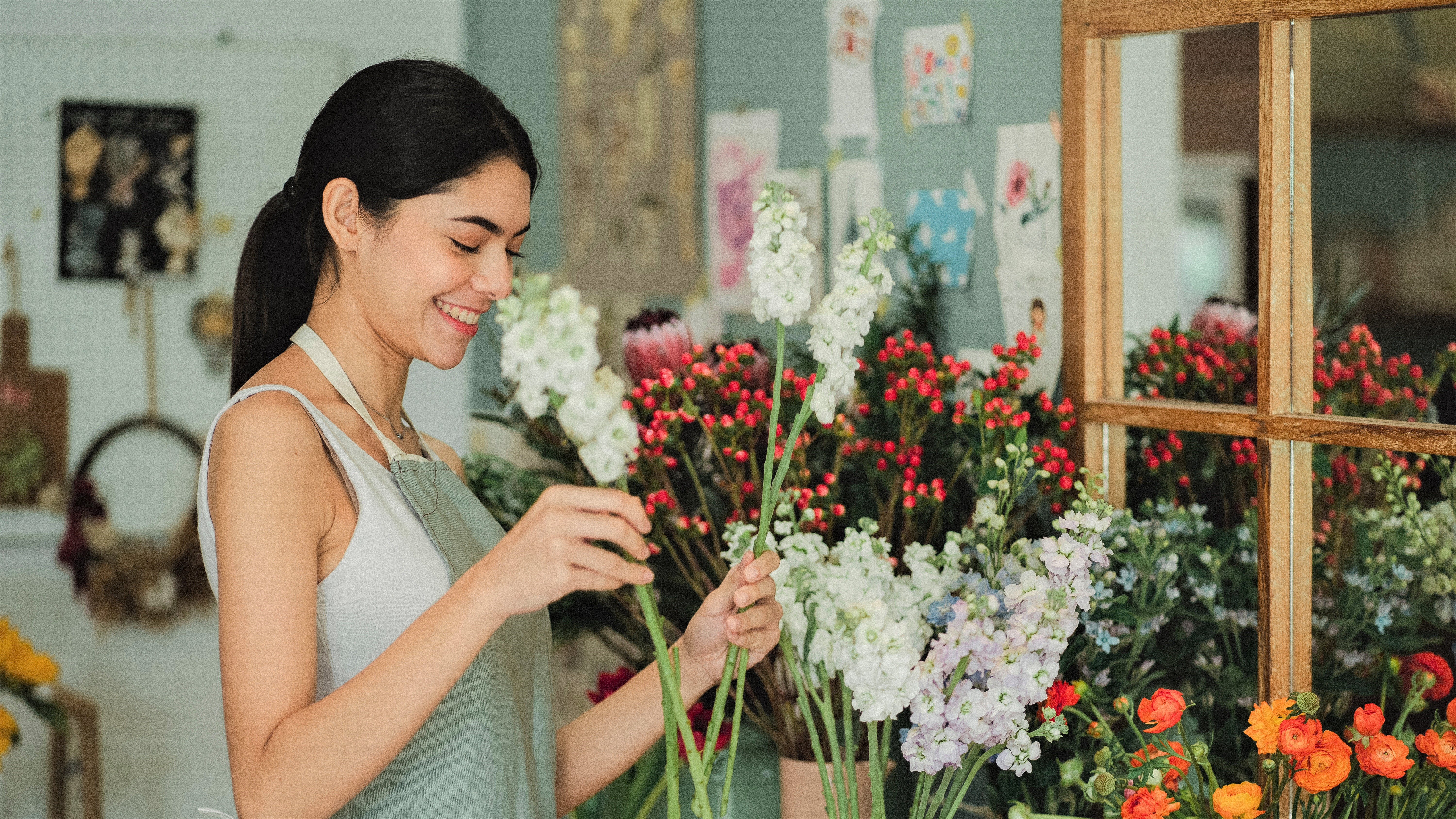 woman placing flowers in a vase in a flower shop
