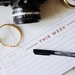 weekly calendar with pen rested across and camera above it